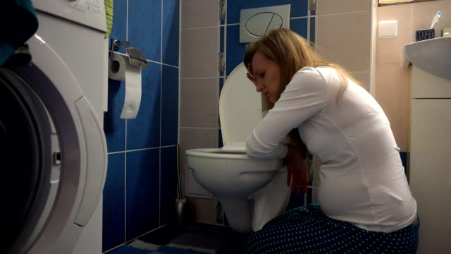 attractive lovely pregnant woman kneeling down and vomiting into toilet video