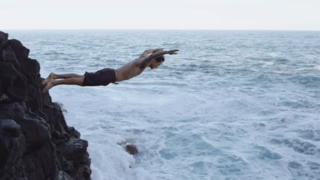 SLO MO Attractive male diving from cliff video