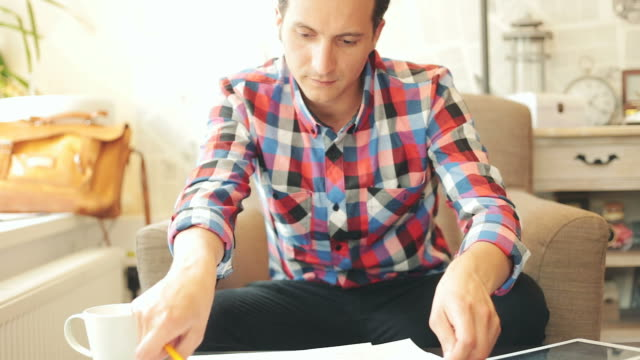 Attractive male working with digital tablet and plans. video