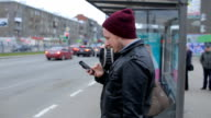 Attractive man looking at mobile phone while waiting in city bus stop video