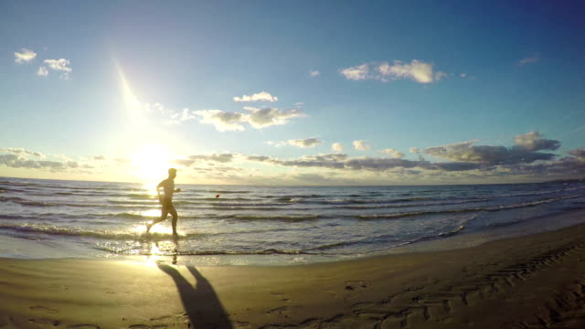 Attractive man running on the beach video