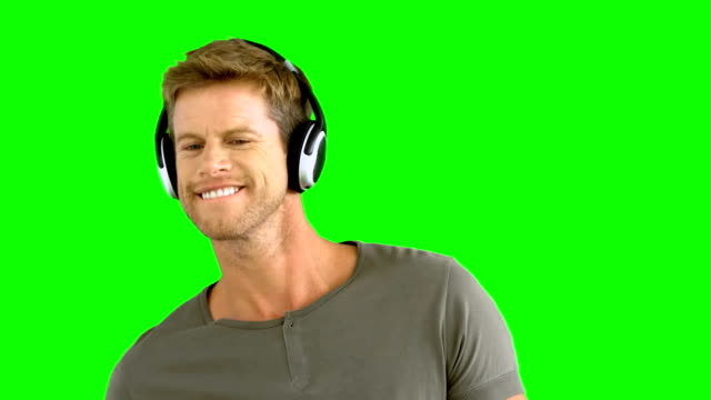 Attractive man with headphones listening to music on green screen video
