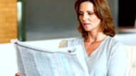 Attractive mature woman reading newspaper video