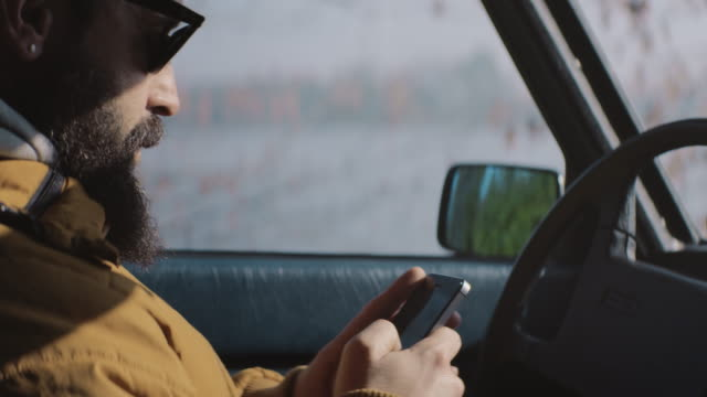 Attractive men text messaging on mobile phone in the car. video