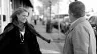 Attractive middle age couple's chance encounter embracing on the street video