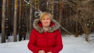 Attractive middle-aged woman smiles and corrects hair. Movie closeup. Quiet winter day in the forest. video