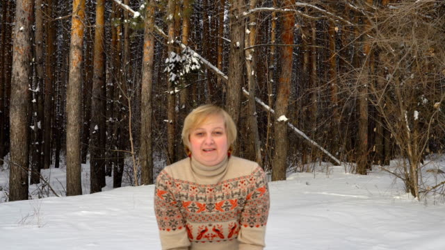 Attractive middle-aged woman throws up soft snow. Woman is pleased the beautiful weather. Movie closeup. Quiet winter day in the forest. video