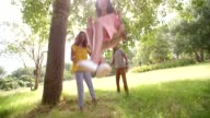 Attractive mother and father takes daughter to park to swing. video