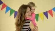 attractive mother is holding cute happy, laughing baby girl in arms and dancing video