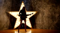 attractive rock girl playing the electric guitar, shining star in the background. slow motion, silhouette video