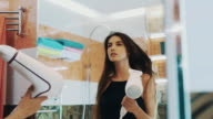 Attractive sexy girl dry hair by hairdryer in bathroom at mirror. Posing video