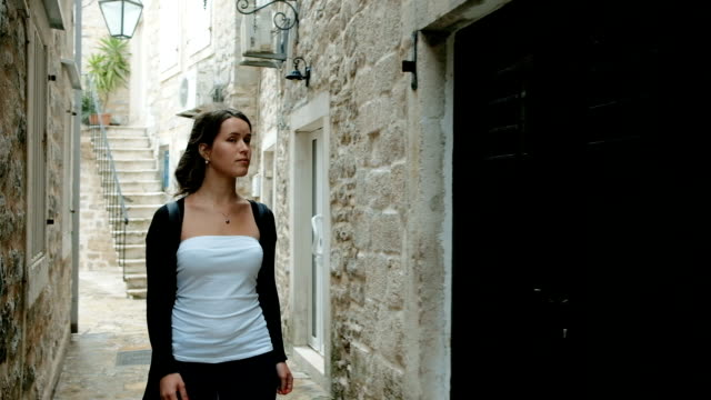 Attractive traveler walks on the narrow streets of old European city video
