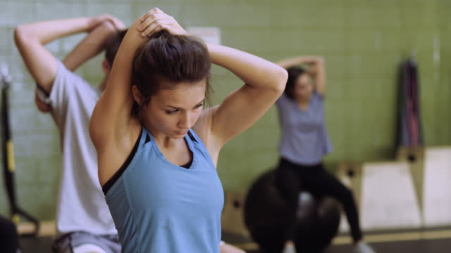 Attractive university aged woman warming up and stretching for a workout video