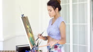 Attractive woman artist painting on her patio video