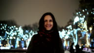 attractive woman at snowy Christmas night smiles looking at the camera in front of park trees decorated sparkling lights video