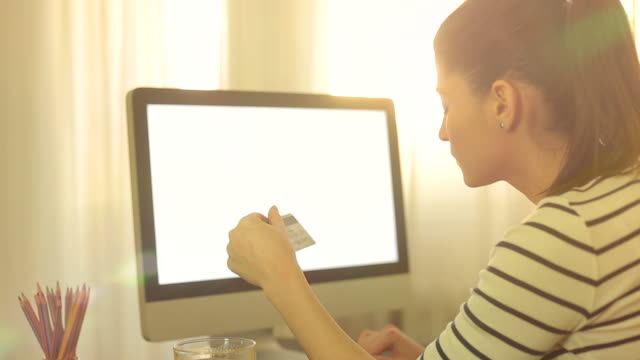 Attractive woman buying online with her credit card using the computer. video