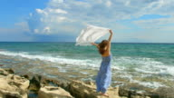 Attractive woman holding white scarf in wind on rocky shore video
