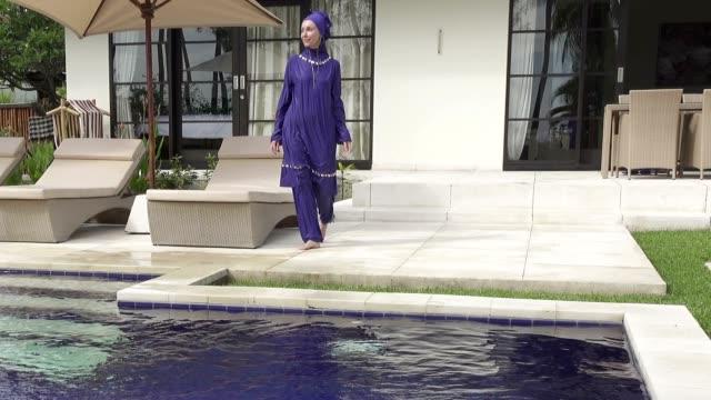 Attractive woman in a Muslim swimwear burkini in the pool video