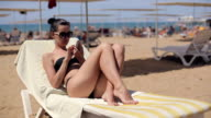 Attractive woman in sunglasses relaxing and using app on smartphone video