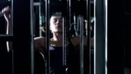 Attractive woman in the gym doing pulldown exercises to front in silhouette video