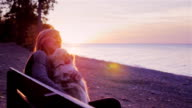 Attractive woman plays with her dog. Sitting on a bench in the park against the backdrop of a beautiful sunset over the sea video