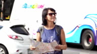 Attractive woman reading tourist map on city street. video