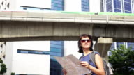 Attractive woman reading tourist map on city street with scytrain at background. video