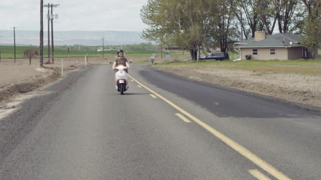 Attractive woman riding on scooter down rural road video