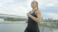 Attractive woman running in the city across a bridge video