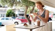 Attractive woman taking picture of a pastry on her mobile video
