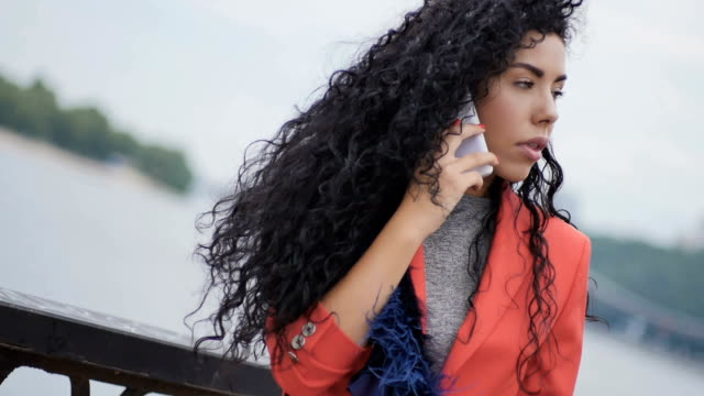 Attractive woman talks on the phone at the bridge video
