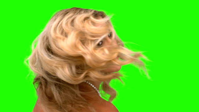 Attractive woman tossing her hair on green screen video