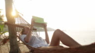 Attractive woman with digital tablet on hammock video
