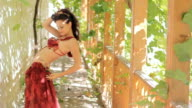 Attractive woman with tattoos dancing belly dance in the gazebo overgrown with vines, slow motion video