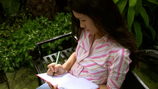 Attractive young asian woman writes. video