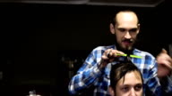 Attractive young barber is cutting human hair with the scissors. He is looking at hair with concentration. The bearded man is raising his chin video