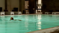 Attractive young blonde woman has a evening swimming in wellness pool video