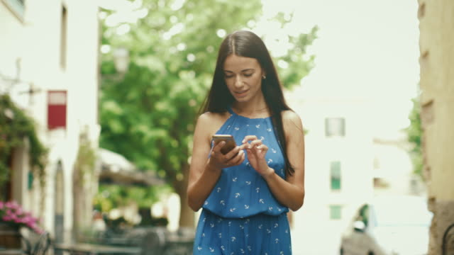 Attractive Young Brunette Woman in Light Summer Dress Walking on Streets of European Town. She is looking at her Mobile Phone and using it. video