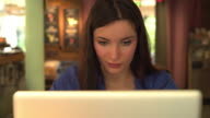 Attractive young brunette woman using a laptop. 1. video