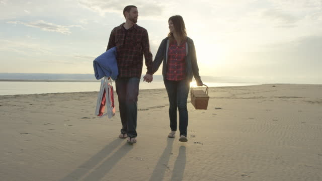 Attractive young couple having a romantic picnic on the beach; walking in slow motion video