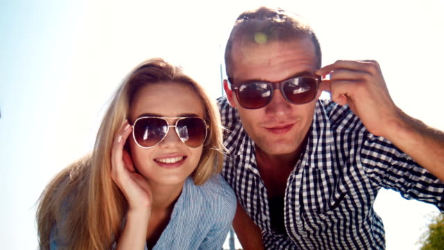 Attractive young couple peering at the camera video