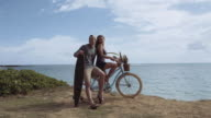 Attractive young couple sitting on bike next to the ocean video