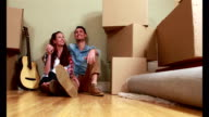 Attractive young couple unpacking boxes video