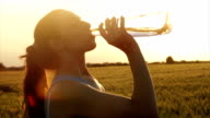 Attractive Young Female Model Drinking Water Bottle Sunset video
