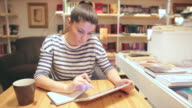 Attractive young female working or maybe studying in the coffee shop. video