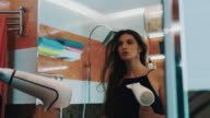 Attractive young girl dry hair by hairdryer in bathroom at mirror. Posing video
