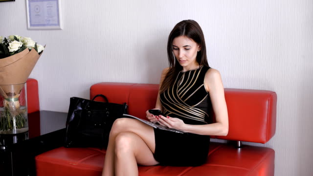 Attractive young girl in black dress chatting on mobile phone, smiling video