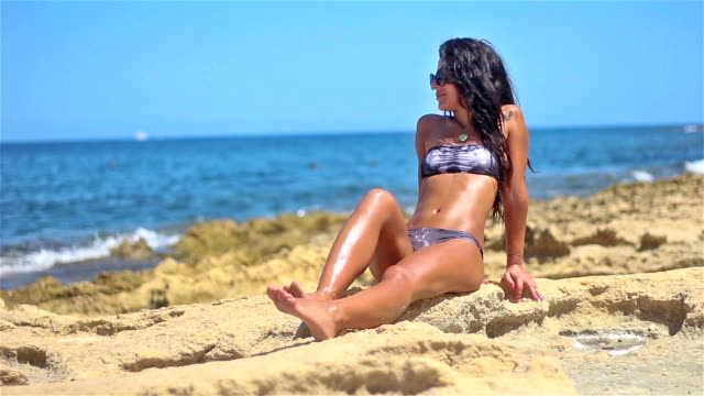 Attractive young girl is lying on rocky sea beach. video