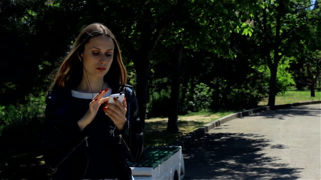 Attractive young girl with smartphone, outdoor video
