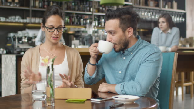 Attractive Young Man and Woman are Sitting Talking at Cozy Coffee Shop. video